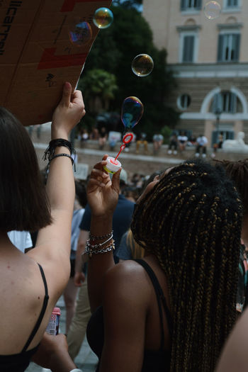 Rear view of women holding bubbles in city