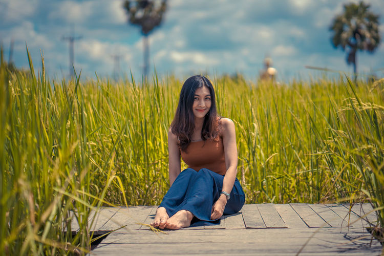 Adult Beautiful Woman Beauty Casual Clothing Contemplation Day Front View Full Length Grass Hairstyle Leisure Activity Lifestyles Looking At Camera Nature One Person Outdoors Plant Portrait Real People Sitting Young Adult Young Women
