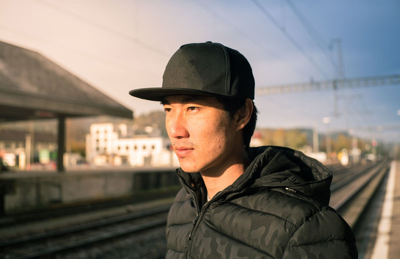 Thoughtful Man Wearing Cap Looking Away At Railroad Station Against Sky