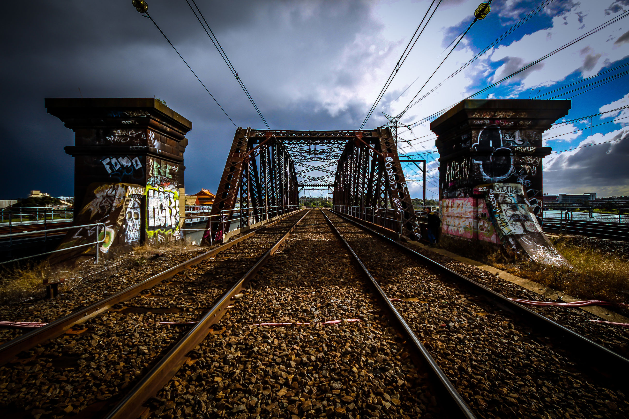 railroad track, rail transportation, sky, architecture, built structure, transportation, diminishing perspective, the way forward, public transportation, connection, cloud - sky, power line, building exterior, vanishing point, railroad station, railway track, cloud, cable, metal, electricity pylon