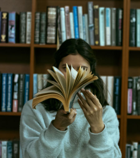 Young woman holding book against shelf in library