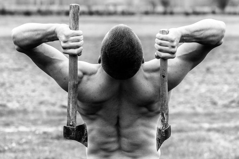 Rear View Of A Shirtless Man Holding Axes