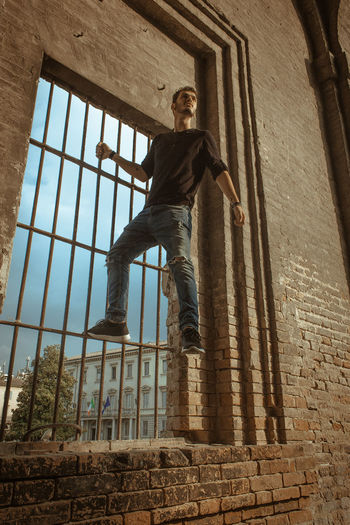 Low angle view of man standing on metal grate in building