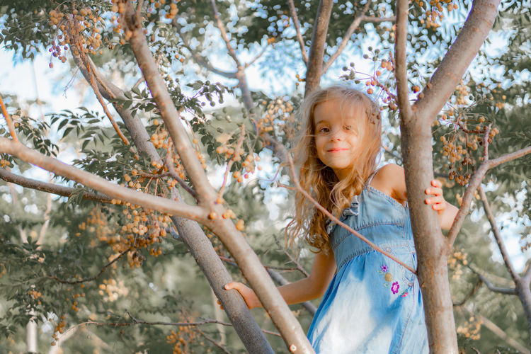 Playful Girl Standing On Branches In Forest