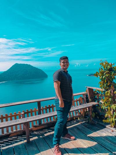 Portrait of man standing on railing against blue sky