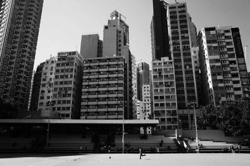 Kid chasing a football amongst the skyscrapers, Wan Chai, Hong Kong. HongKong Streetphotography Black And White Monochrome