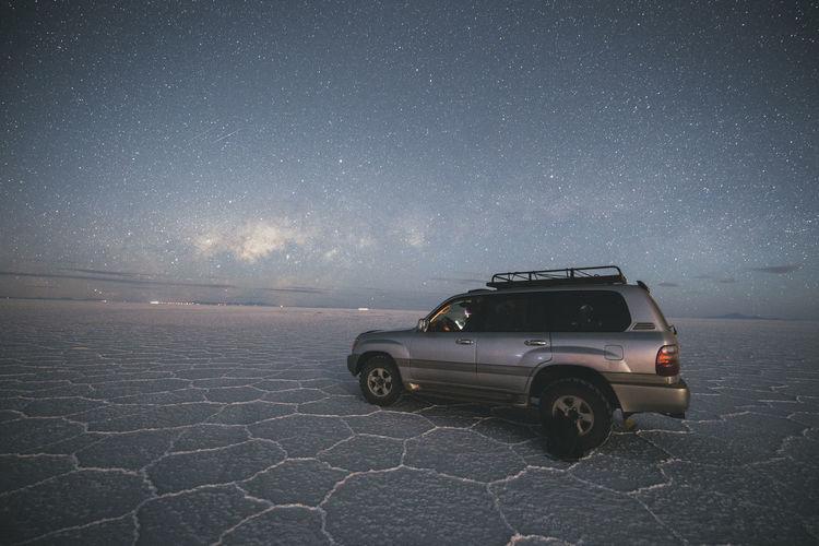 Car on desert against sky at night