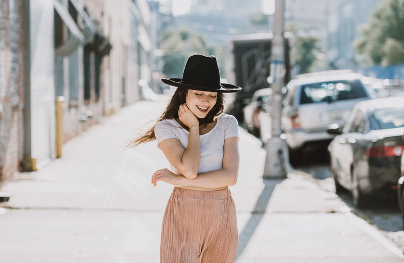 Full length of woman wearing hat standing in city