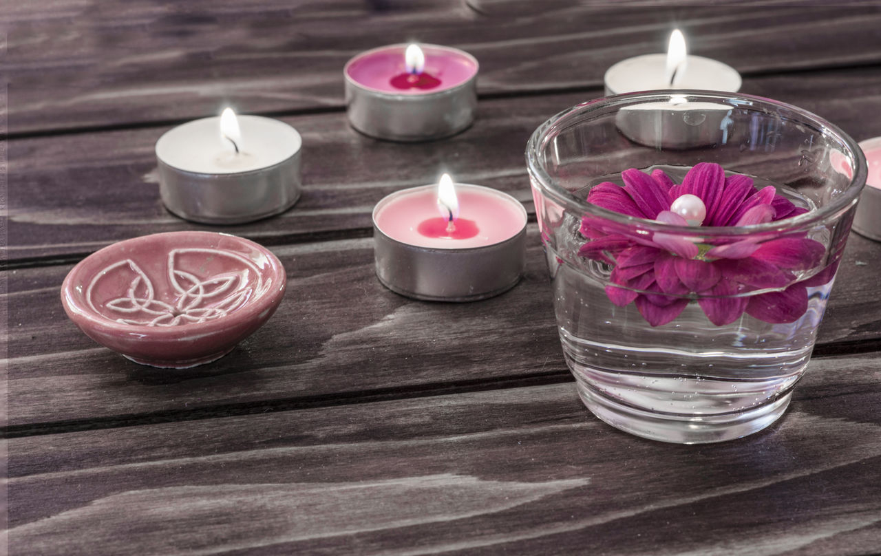 candle, flame, burning, tea light, table, petal, no people, flower, indoors, close-up, high angle view, pink color, aromatherapy, wood - material, spirituality, freshness, water, rose petals, nature, health spa, day