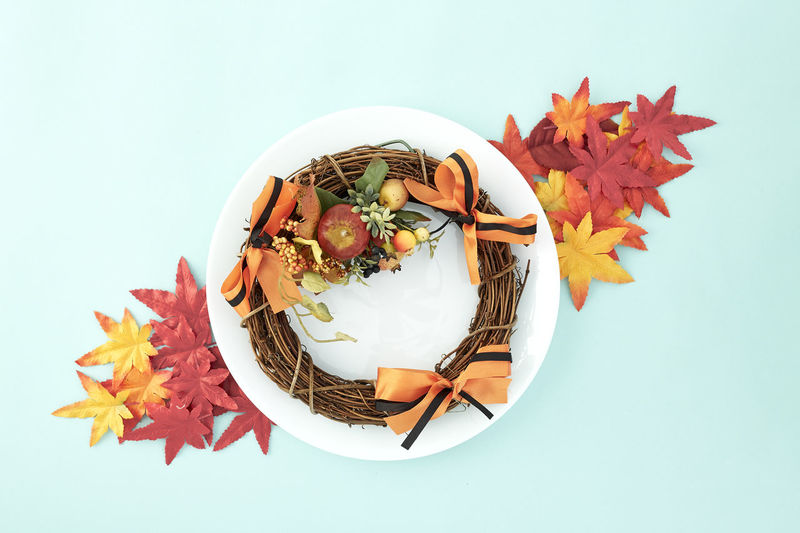 White dish with wreaths and autumn leaves decorative Halloween on pastel pale blue background, with copy space for text. Flat lay. Sales Holiday Flyer Banner Poster Travel Traveling Traveler Vacation Trip Sale Template Mockup Abstract Art Autumn Leaves Falling 2019 2020 Wreath New Year Halloween Autumn Leaves Autumn Background Plate Minimal Flat Lay Fall Background Leaf Design Frame Orange Concept Composition Green Maple Bright Pattern Forest Decoration Studio Shot Plant Part White Background Still Life Indoors  No People Food Food And Drink Close-up Copy Space Nature High Angle View Orange Color Table Freshness Fruit Plant Maple Leaf