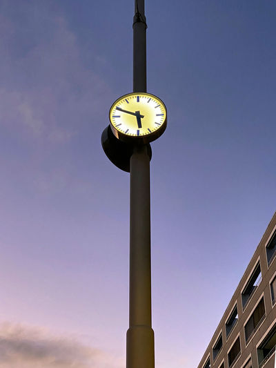 Low angle view of clock on pole against building