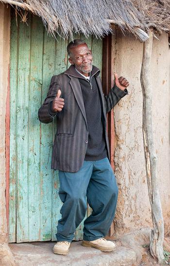 Portrait of mature man standing outside hut