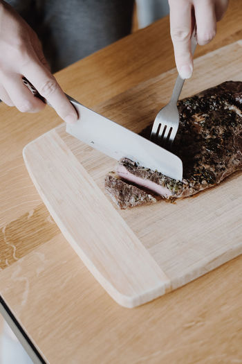 High angle view of woman preparing food on cutting board