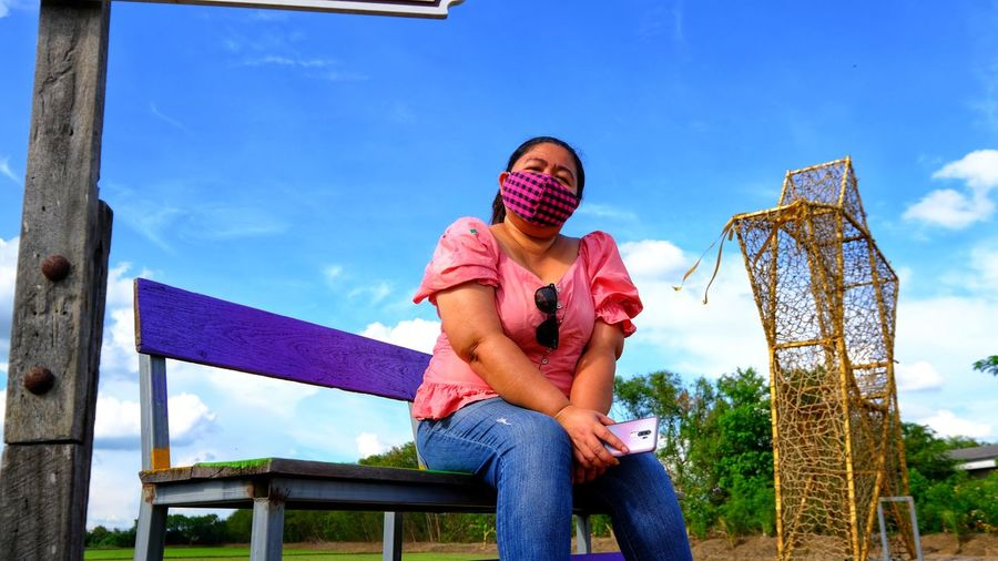 Portrait of woman wearing mask while sitting on bench against sky