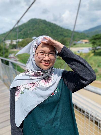 Portrait of smiling girl wearing hijab standing on footbridge