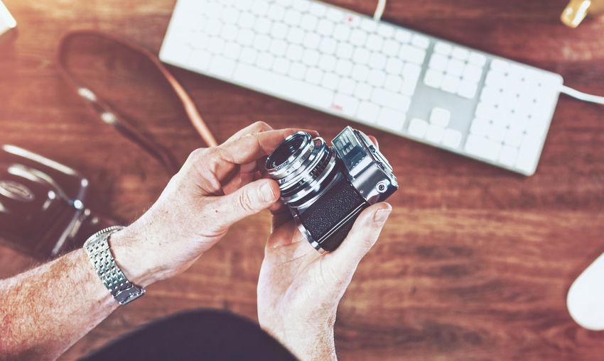 Cropped image of men holding camera