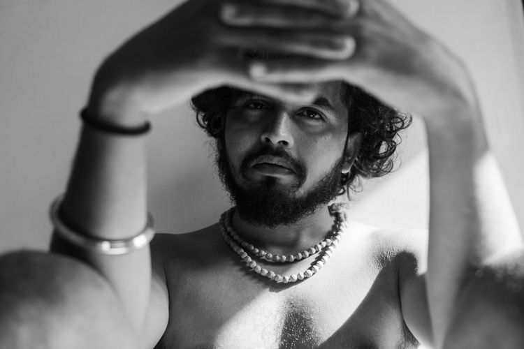 Portrait of shirtless man holding camera
