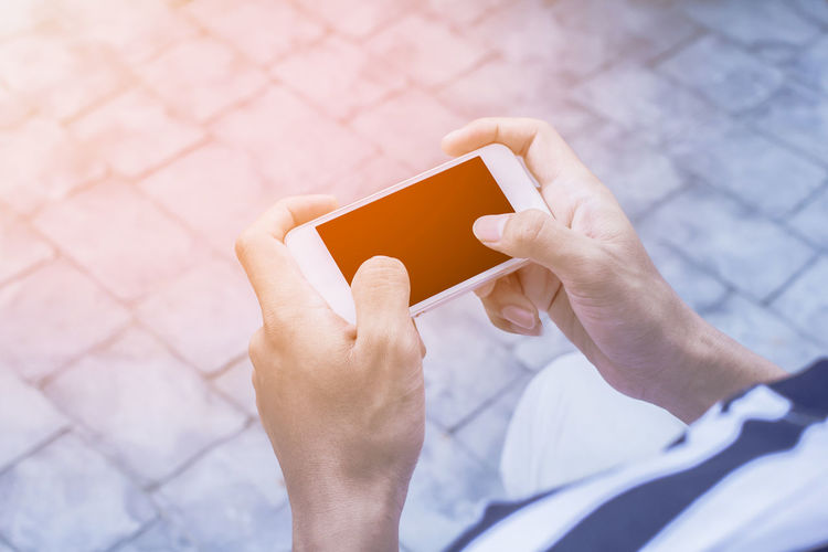 Midsection of man using mobile phone on footpath