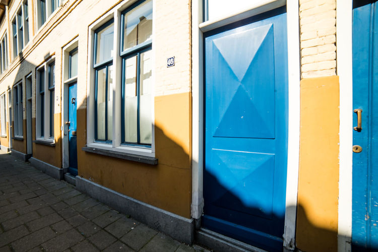 Blue and yellow Building Exterior Architecture Built Structure Building Door Day No People Window Entrance Yellow Glass - Material Outdoors Closed City Wall Sunlight Street Multi Colored Wall - Building Feature Blue