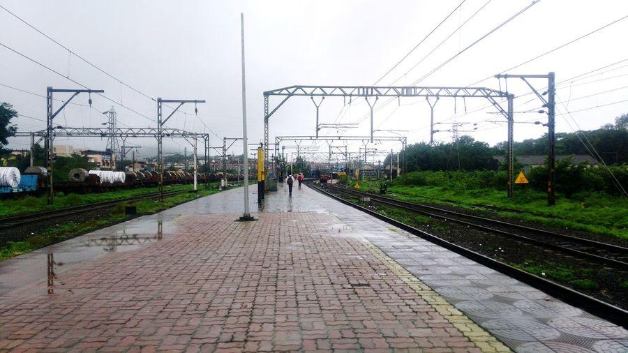 Railroad tracks against sky during rainy season