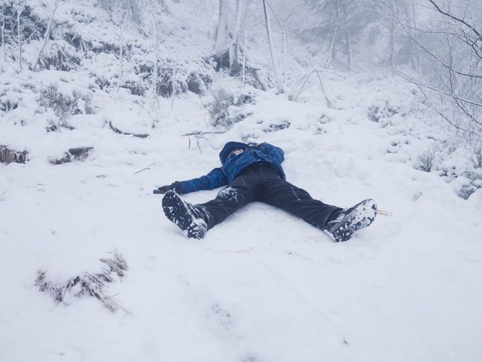 High angle view of person lying on snow covered land