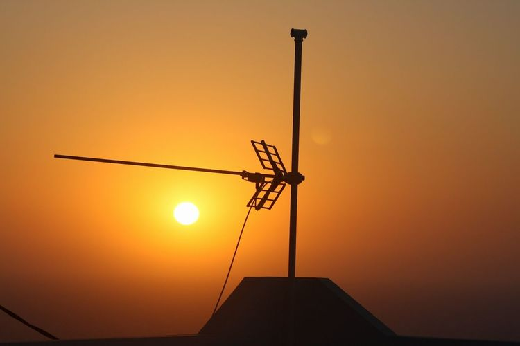 Low angle view of silhouette windmill against orange sky