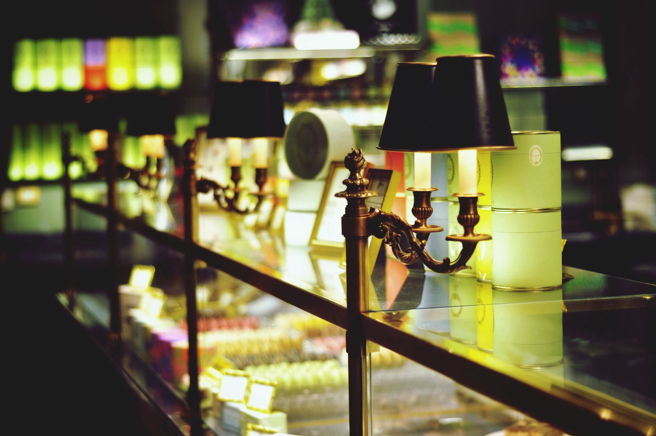indoors, focus on foreground, selective focus, lighting equipment, illuminated, metal, close-up, bicycle, night, no people, hanging, in a row, technology, metallic, built structure, still life, equipment, electricity, protection