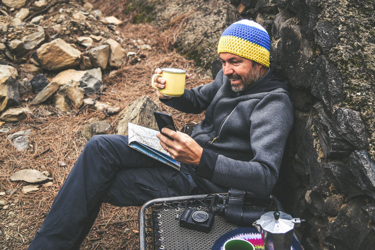 Bearded middle-aged man with woolen hood and sunglasses resting sitting after trekking day Male drinking coffee shooting selfie, chatting with friends. Relaxing with hot beverage in a National Park Sitting Real People Winter Technology One Person Lifestyles Clothing Communication Knit Hat Leisure Activity Activity Warm Clothing Day Wireless Technology Nature Land Hat Men Holding Outdoors