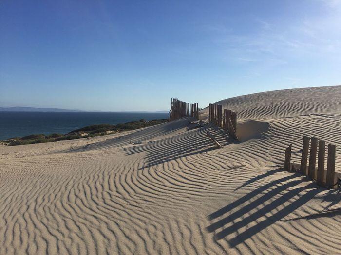 Sand dunes at punta paloma beach against sky