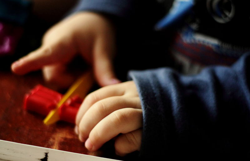 Cropped hands of child cutting crayon on table