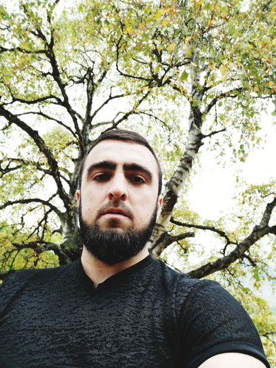 Portrait of young man against tree