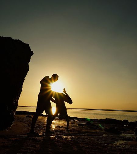 Silhouette man helping friend handstand at beach against sky during sunset