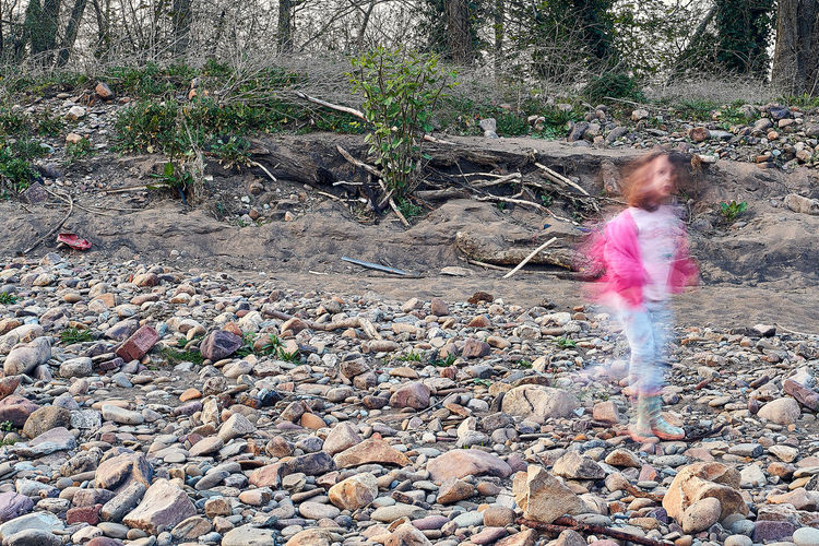 Blurred motion of girl standing on rock