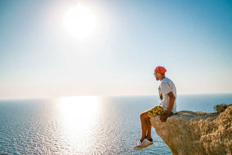 Man sitting on rock over sea against sky