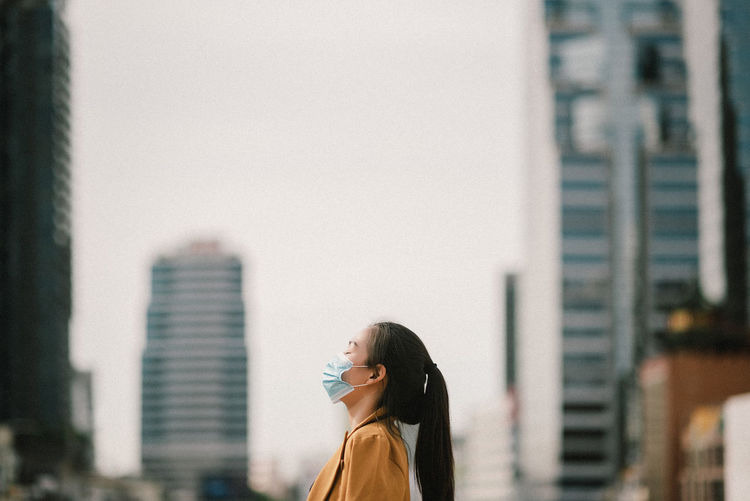 Side view of businesswoman wearing mask standing outdoors