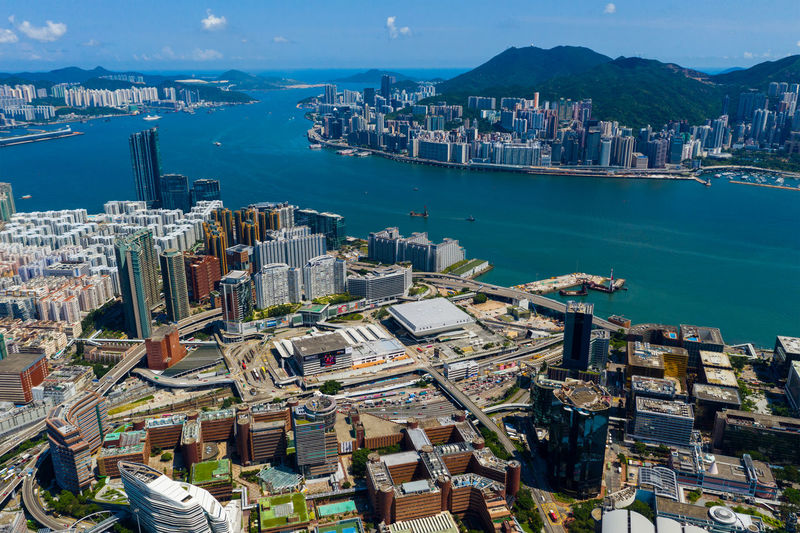 High angle view of city by sea and buildings against sky