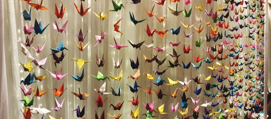 Full frame shot of colorful paper cranes hanging against curtain
