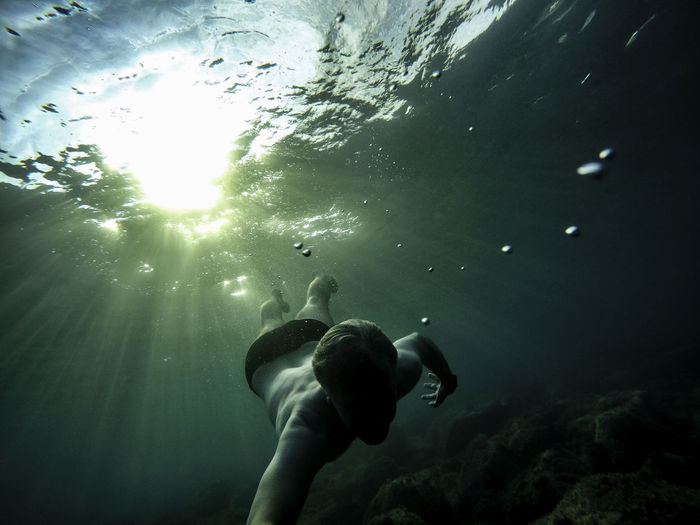 Low angle view of man swimming in sea