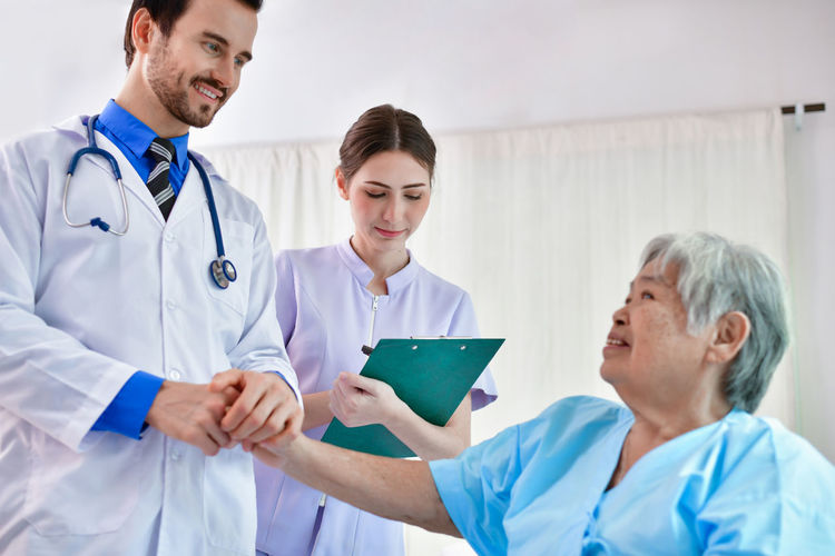 Smiling Doctor Holding Hands Of Senior Woman In Hospital