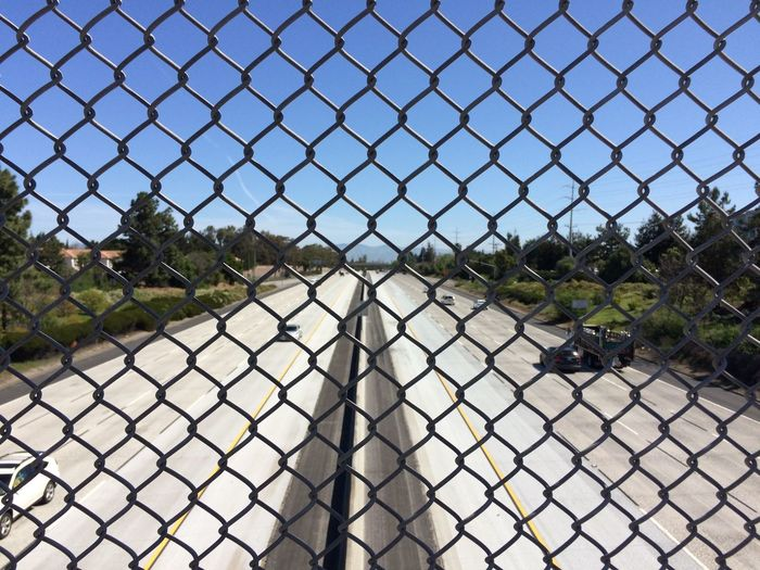 Cars on road seen through chainlink fence