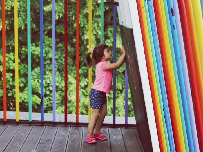 Girl Drawing On Blackboard By Colorful Railing On Porch