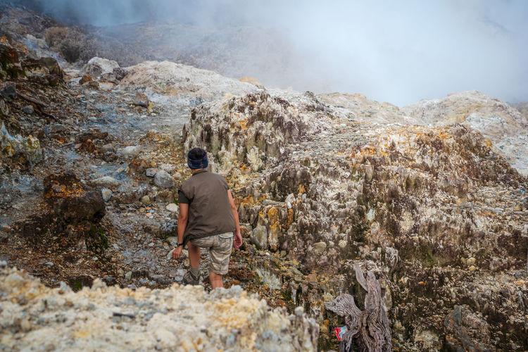 Rear view of people walking on rocks against mountain