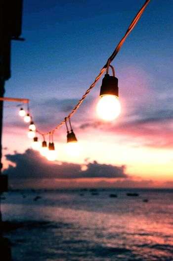 Hanging Dusk Sunset Outdoors Sun Sea Water Illuminated Nature Beach Sky No People Vacations Beauty In Nature Close-up
