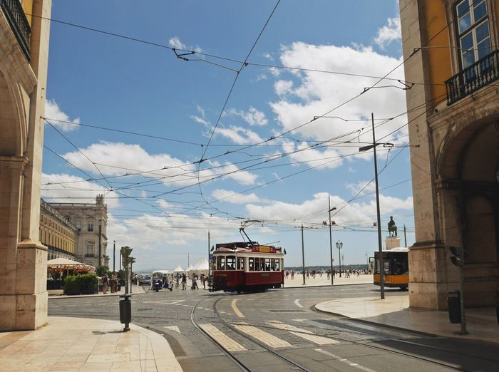 Tramway On City Street Amidst Buildings Against Sky