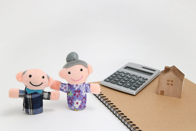Close-up of figurines by spiral notebook and calculator against white background