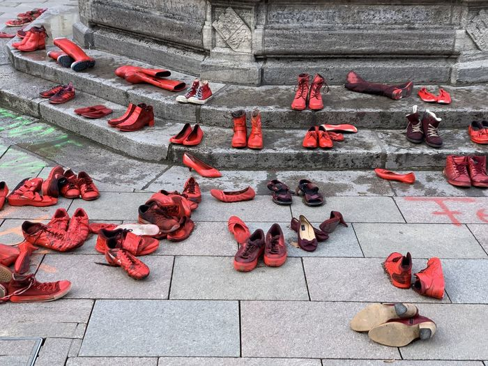 High angle view of red shoes in public on footpath in city, artistic