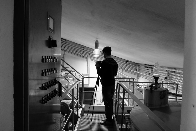 Silhouette Man Standing On Elevated Walkway In Illuminated Building