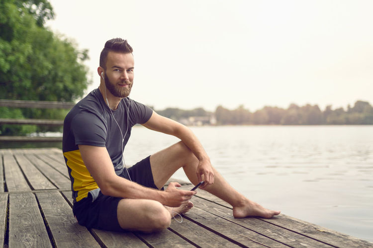 Full Length Portrait Of Smiling Handsome Man Sitting On Boardwalk By Lake