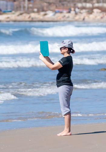 Acre, Israel - March 04, 2017 : Woman photographing the coast and Mediterranean Sea and surf on your mobile tablet in Acre beach, Israel Beach Beautiful Camera Coast Communication Day Happy Lady Mobile Nature One Person One Woman Only Outdoors People Sand Sea Smart Tablet Technology Technology Photography Using Vacation Vacations Water Woman