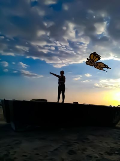 Close-up of butterfly flying with woman in background against sky